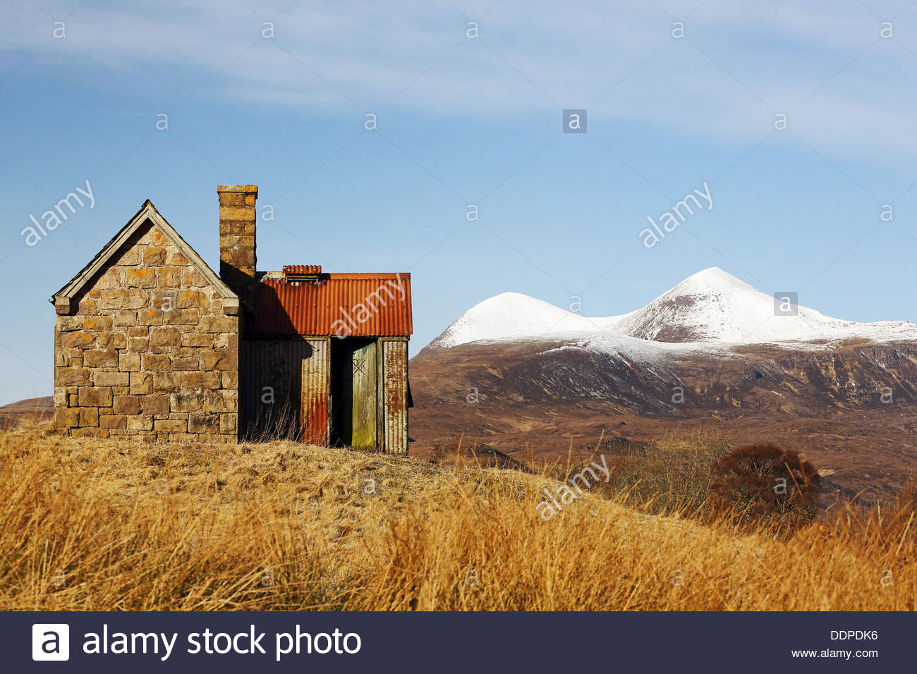 An old deserted stone hut on a hill with the mountain of Ben More in the distance. From Sutherland in the Scottish highlands. - Stock Image
