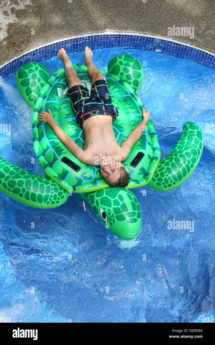 Young boy laying on inflatable turtle in pool - Stock Image