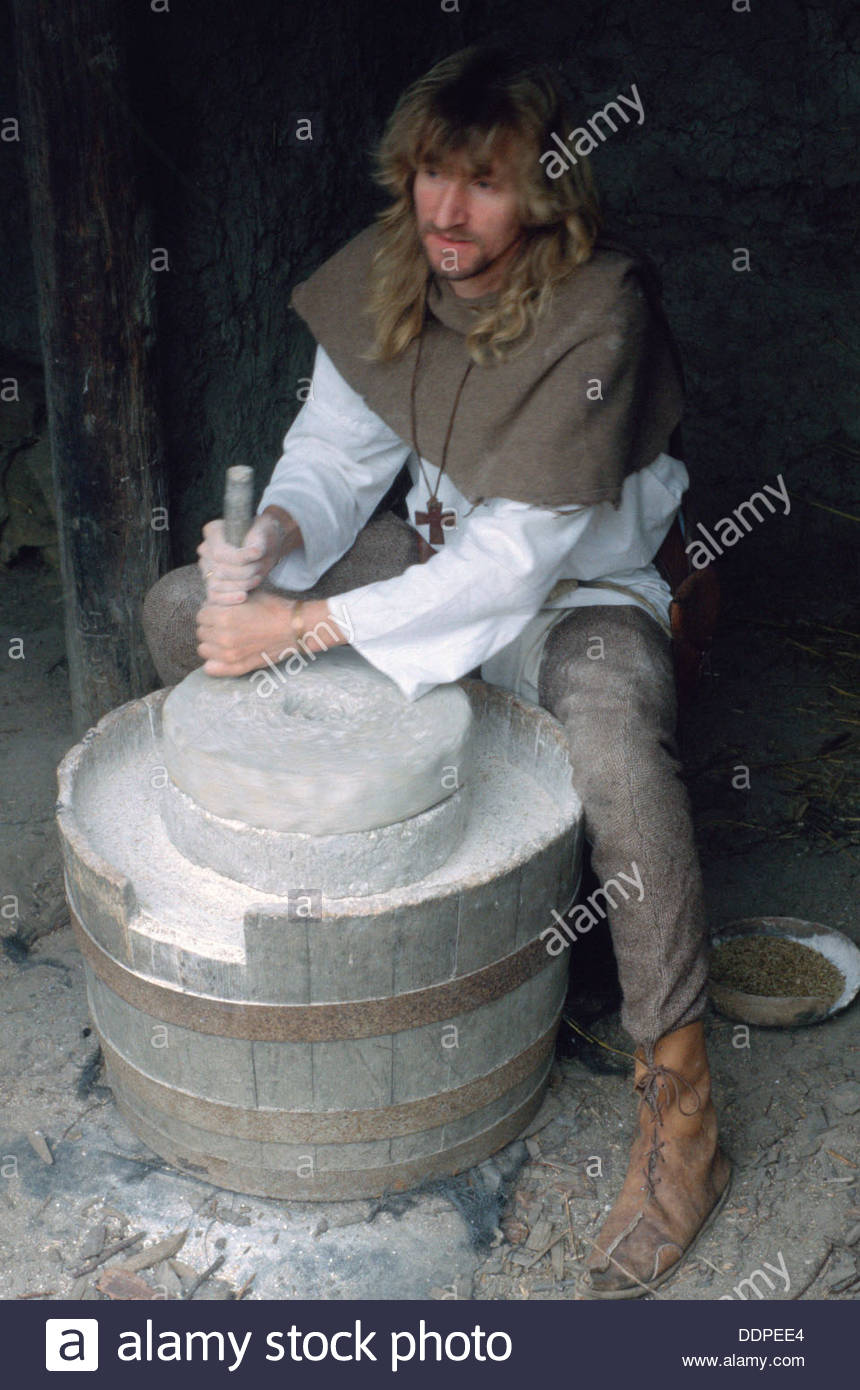 man-in-medieval-dress-grinding-rye-with-a-quern-stone-museum-of-farming-DDPEE4.jpg
