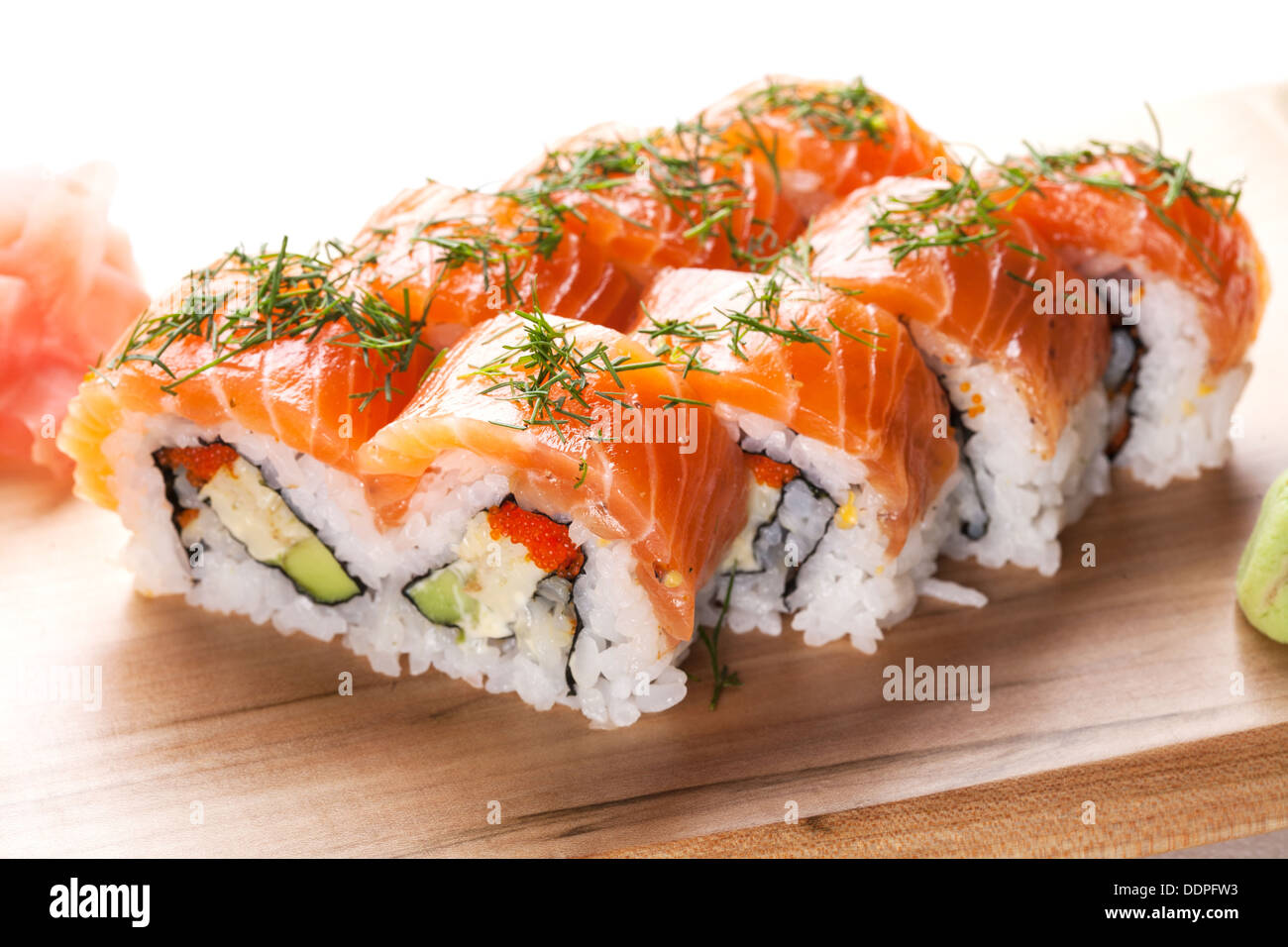 Salmon sushi rolls on wooden plate. - Stock Image