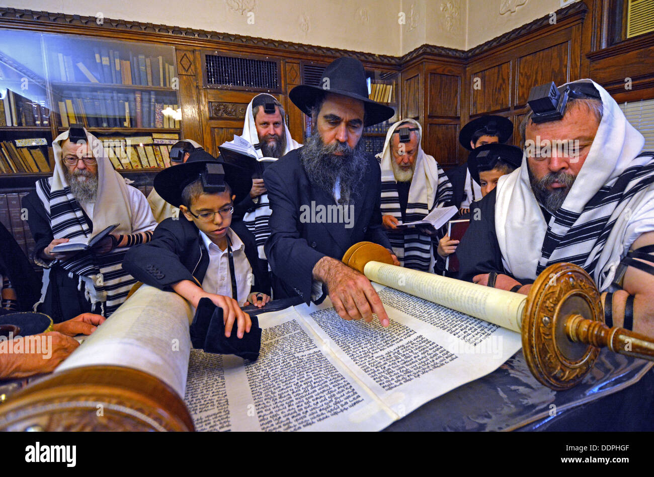 Weekday morning services in the Rebbe's office. Boy called to the Torah for his Bar Mitzvah - Stock Image