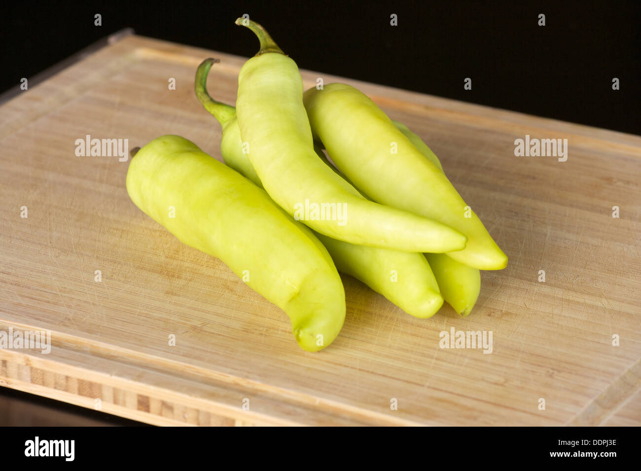 banana peppers on a cutting board - Stock Image