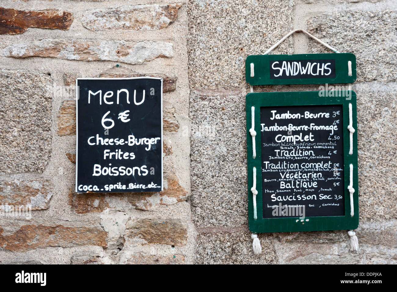 Menus on a wall outside a restaurant at Concarneau Brittany France - Stock Image