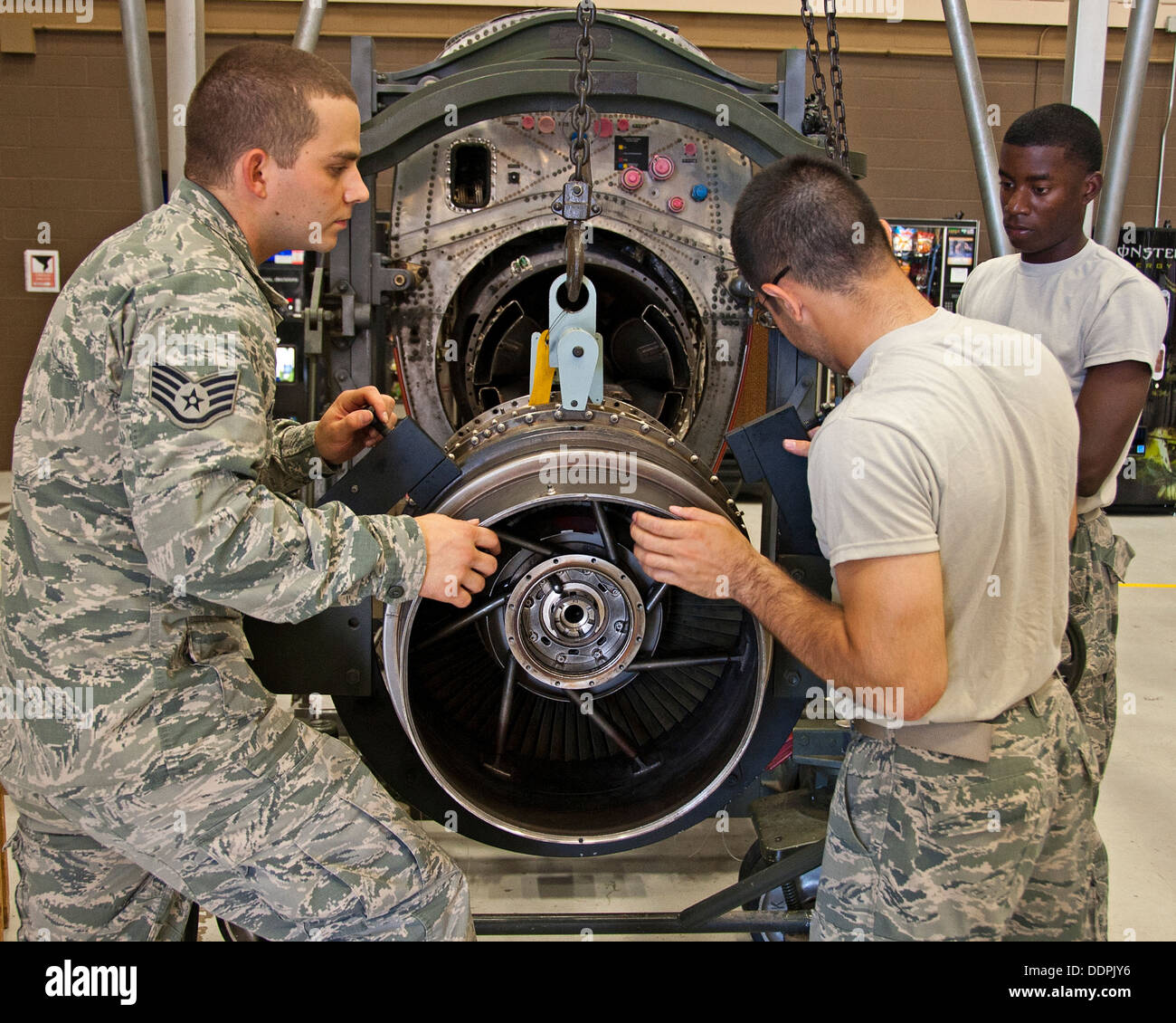 U.S. Air Force Instructor Staff Sgt. Christopher Walker, Airman Vivek Lebouef and Harold Griffen, 361st Training Squadron, Jet Propulsion course are removing an engine turbine from a C-130 aircraft on August 27, 2013 at Sheppard Air Force Base, Texas. - Stock Image