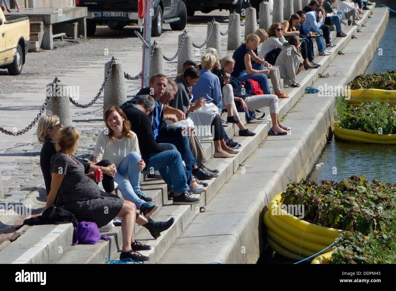 City Dwellers People relaxing on river quay on a regular working day during lunchtime. Rosenlund, Gothenburg, Sweden - Stock Image