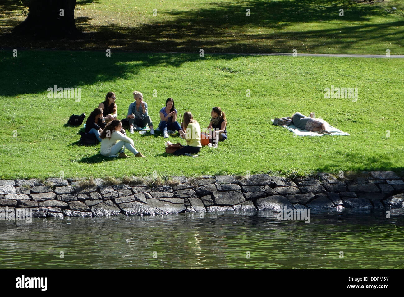 Girls have a picnic on the riverbank in a park, Gothenburg, Sweden - Stock Image