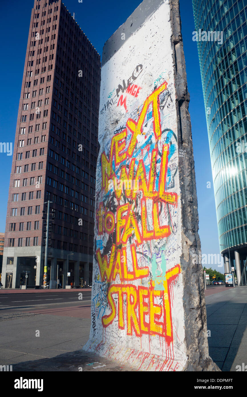 Small remaining section of Berlin Wall on Potsdamer Platz Graffiti 'Next Wall To Fall Wall Street' Berlin Germany - Stock Image