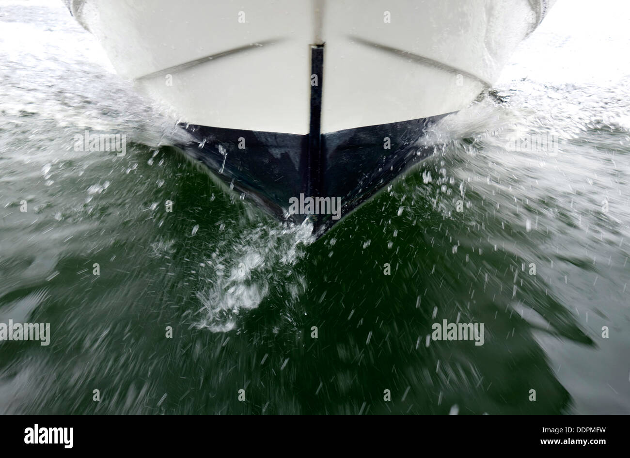 Collision Unavoidable. The prow of a boat in speed cuts through the water in viewer direction. - Stock Image