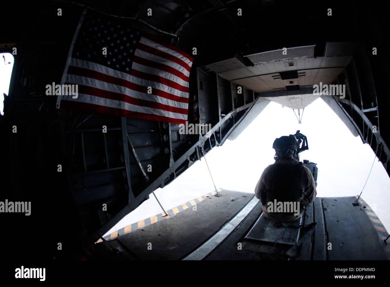 U.S. Marine Corps Cpl. Ryan P. Wells, a crew chief with Marine Heavy Helicopter Squadron 462 (HMH-462), provides aerial security over Helmand province, Afghanistan, Aug. 31, 2013. HMH-462 transported Marines with Golf Company, 2nd Battalion, 8th Marines, Stock Photo