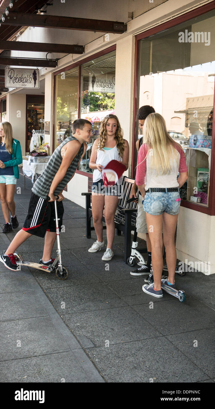 2 good looking young teen boys with kick scooters schmoozing with 2 pretty long haired teen girls on Main street Edmonds WA - Stock Image