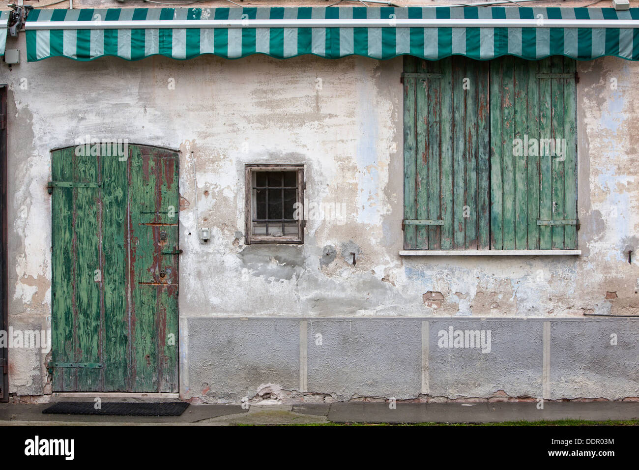 Fabulous Detail of old stucco house with crumbling facade, green wooden  QR53