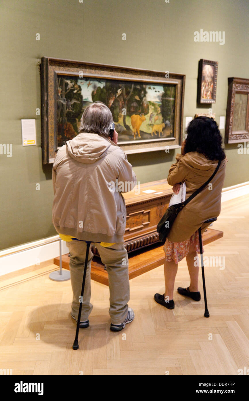 A couple sitting on shooting sticks appreciating art paintings, The Ashmolean Museum, Oxford UK - Stock Image