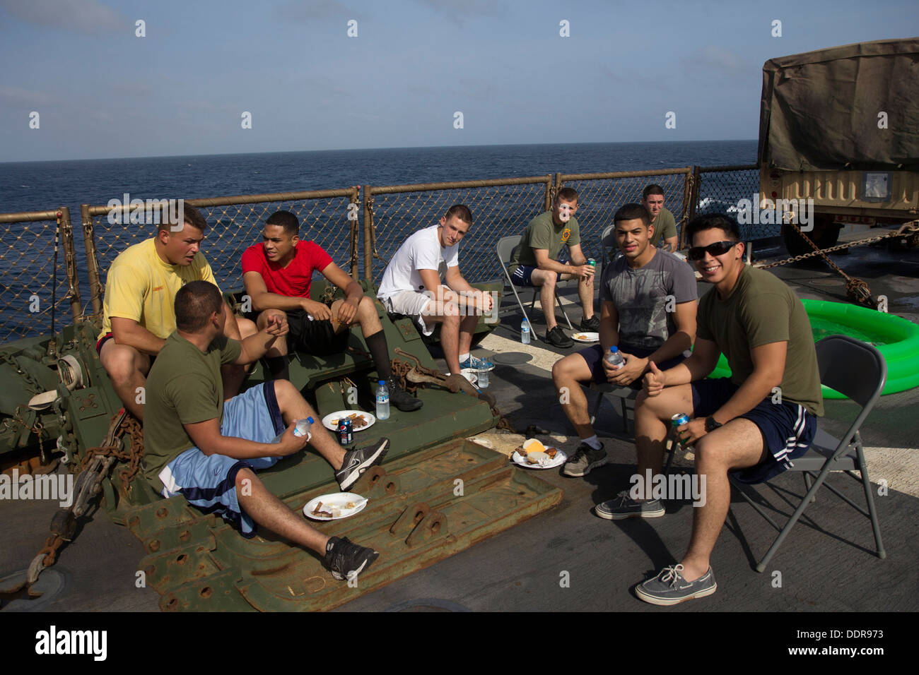 U.S. Marines and Sailors assigned to the 26th Marine Expeditionary Unit (MEU) and USS Carter Hall (LSD 50) relax out of uniform - Stock Image