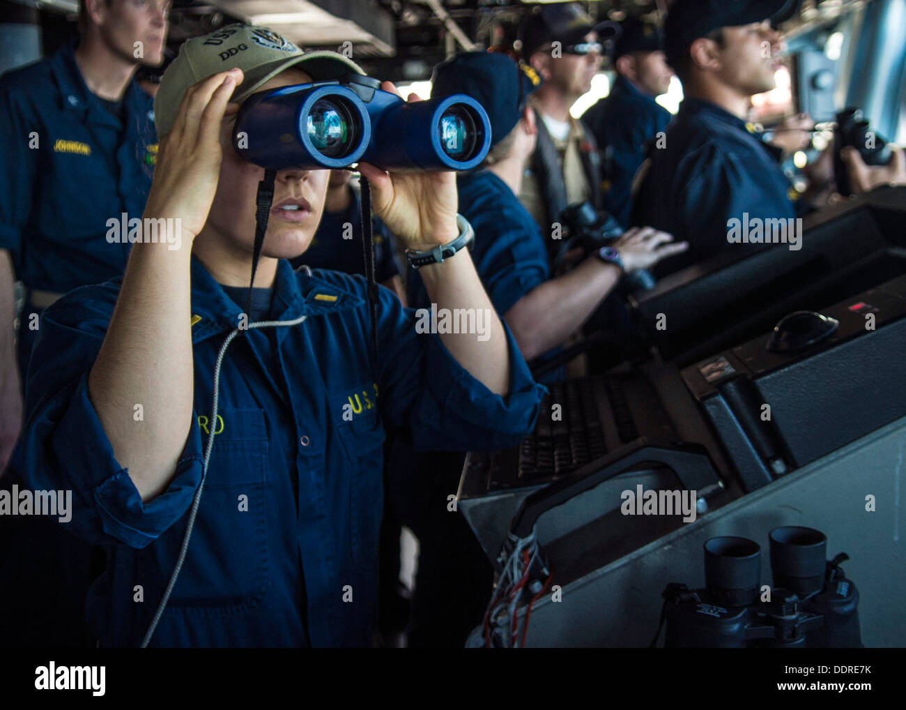 Ensign Jane Baird observes surface contacts from the bridge of guided-missile destroyer USS Higgins (DDG 76) as the ship pulls - Stock Image