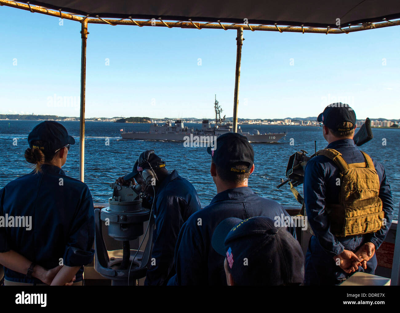Sailors observe the Japan Maritime Self-Defense Force destroyer Takanami (DD 110) from the bridge wing of the guided-missile destroyer USS Higgins (DDG 76) as the ship pulls out of Fleet Activities, Yokosuka. Higgins is on patrol in the U.S. 7th Fleet are - Stock Image