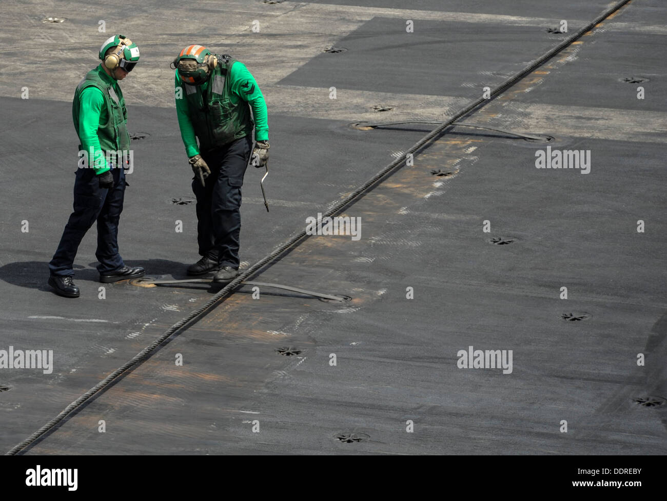 Aviation boatswain's mates (equipment) inspect arresting gear cables prior to flight operations aboard the aircraft carrier USS - Stock Image