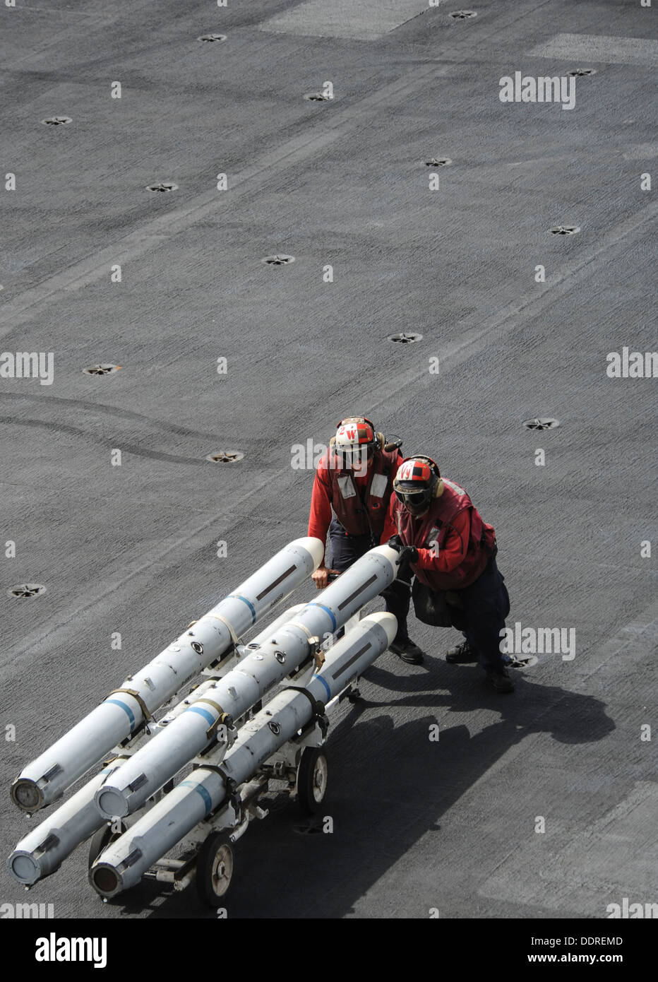 Aviation Ordnancemen 3rd Class Brendan Tuller, left, and Lashell Richmond, both assigned to the Argonauts of Strike Fighter Squadron (VFA) 147, push ordnance across the flight deck of the aircraft carrier USS Nimitz (CVN 68). The Nimitz Carrier Strike Gro - Stock Image