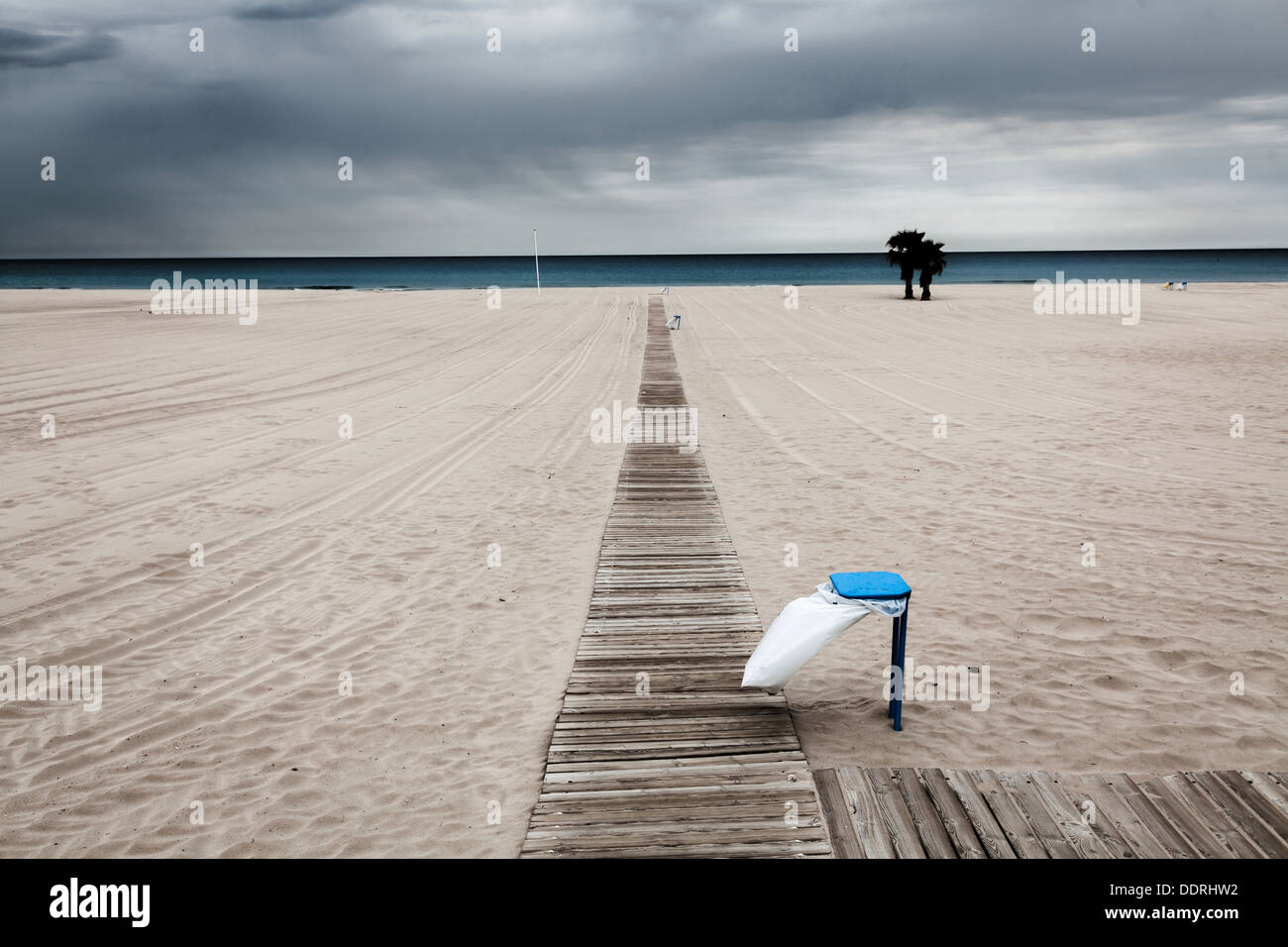 empty beach on an overcast windy day with rubbish bin - Stock Image