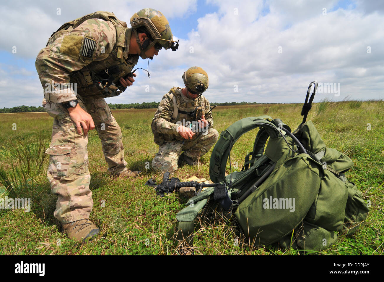 U.S. Air Force Staff Sgt. Kane Lawlor (left), and Airman First Class Joshua Darins (right) use radios to communicate with a UH-60 Black Hawk helicopter from the New Jersey Army National Guard's 1-150 Assault Helicopter Battalion during training at Warren - Stock Image
