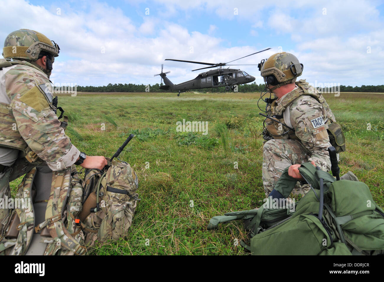 U.S. Air Force Staff Sgt. Kane Lawlor (left), and Airman First Class Joshua Darins (right) prepare to board a UH-60 Black Hawk helicopter from the New Jersey Army National Guard's 1-150 Assault Helicopter Battalion during training at Warren Grove Gunnery - Stock Image