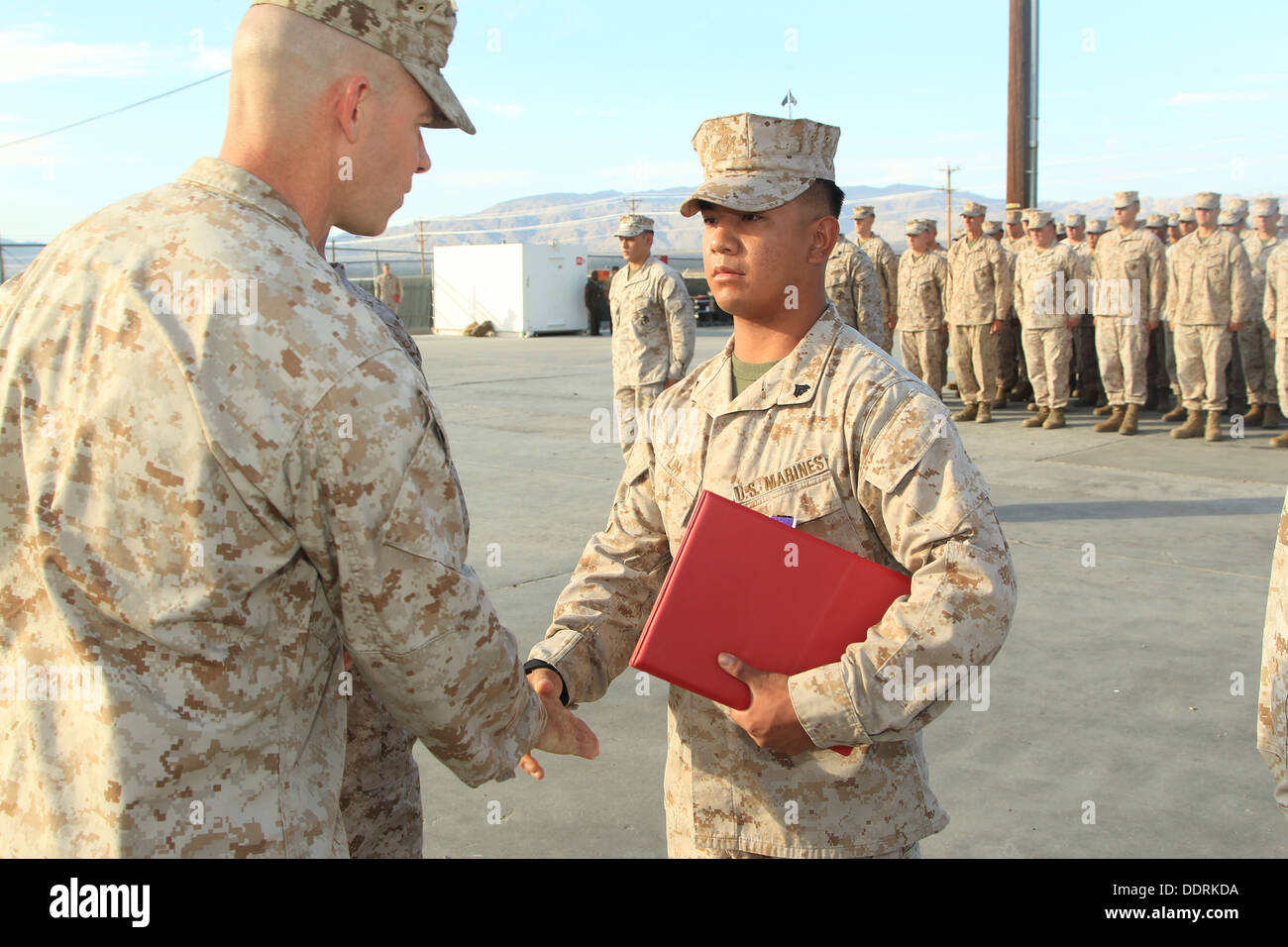 Cpl. Phillip V. Lim, tank crewman, Co. D, 1st Tank Battalion, is presented with a Purple Heart by Maj. Andrew Dirkes, executive - Stock Image
