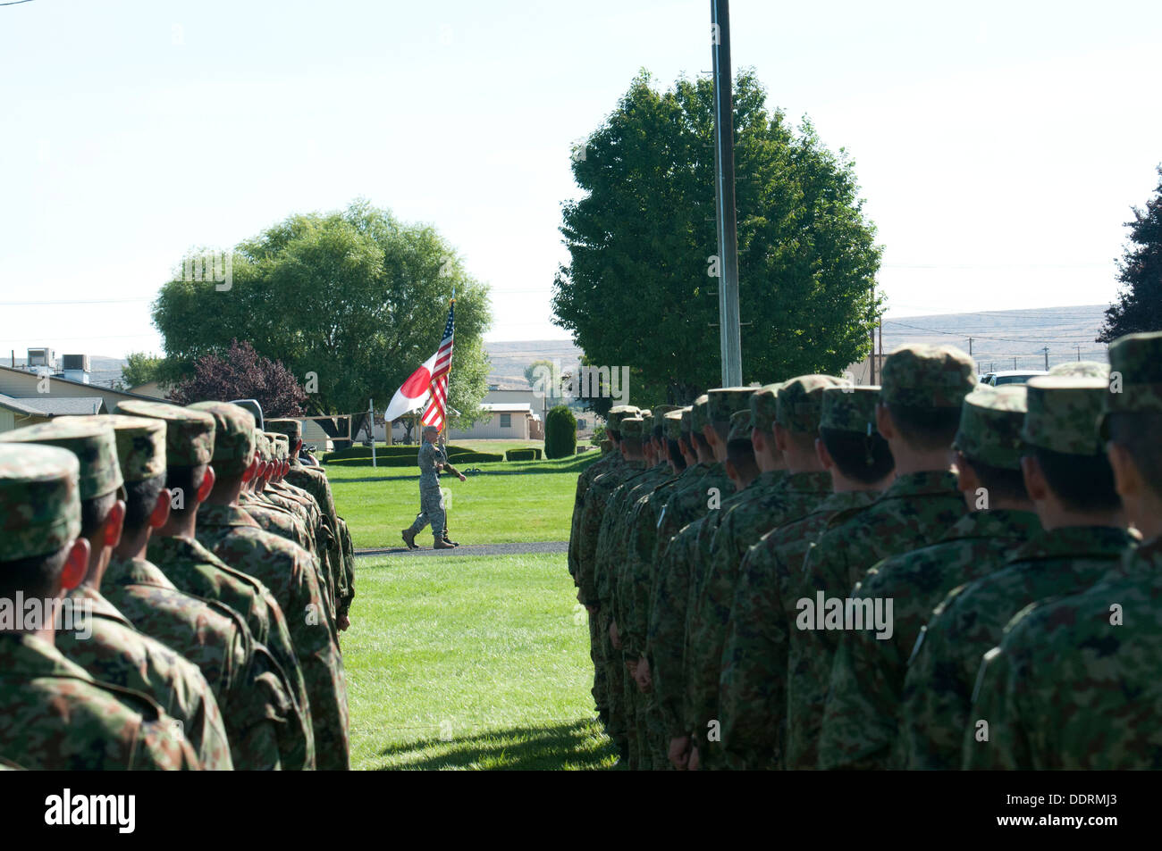 Soldiers from 16th Japan Ground Self-Defense Force Regimental Combat Team, 4th Division, stand at attention while the U.S. and Japanese colors are retired during an opening ceremony for Operation Rising Thunder Sept. 4 at the Yakima Training Center, Wash. - Stock Image