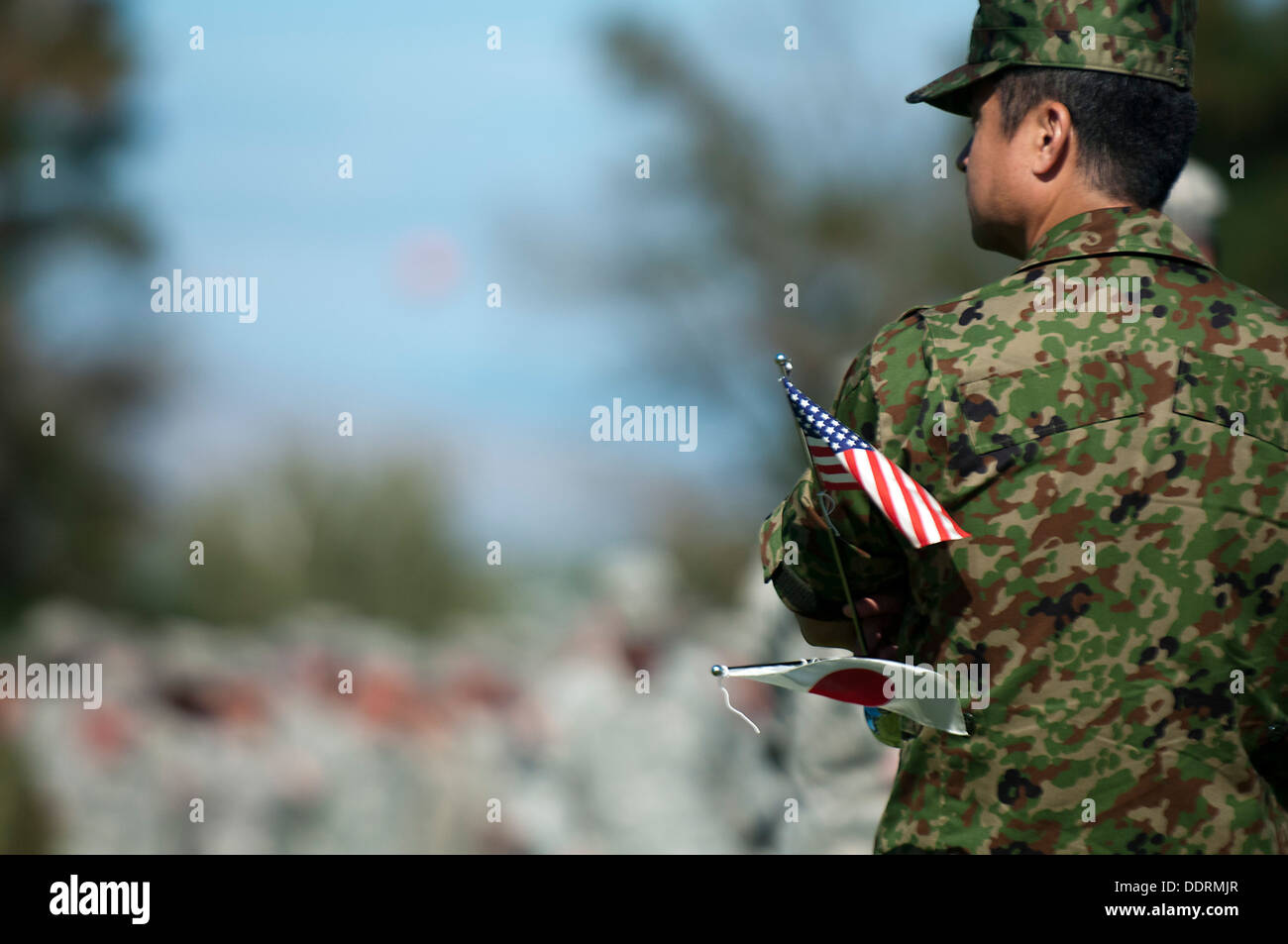 A soldier from 16th Japan Ground Self-Defense Force Regimental Combat Team, 4th Division, holds miniature U.S. and Japanese flags following the opening ceremony for Operation Rising Thunder Sept. 4 at the Yakima Training Center. The exercise aims to impro - Stock Image