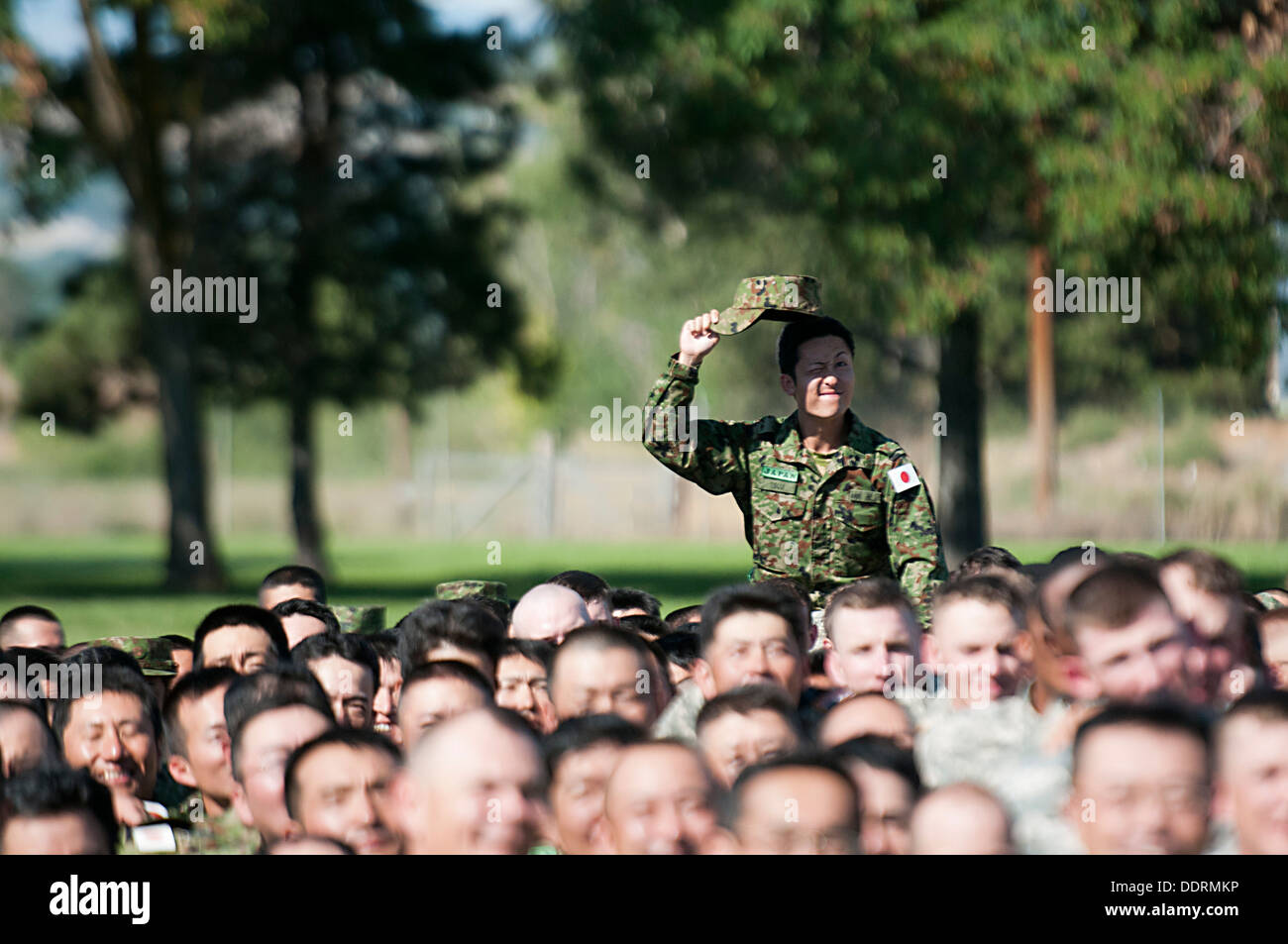 A soldier from 16th Japan Ground Self-Defense Force Regimental Combat Team, 4th Division, raises his hat while sitting on the shoulders of a fellow soldier during a group photo following the opening ceremony for Operation Rising Thunder Sept. 4 at the Yak - Stock Image