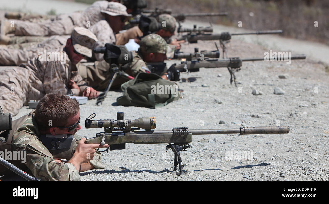 British Royal Army commandos take aim with M40A5 sniper rifles alongside Marines with 1st Air Naval Gunfire Liaison Company during joint training Exercise Burmese Chase aboard Camp Pendleton, Calif., Sept. 3, 2013. The training exercise was designed to in - Stock Image