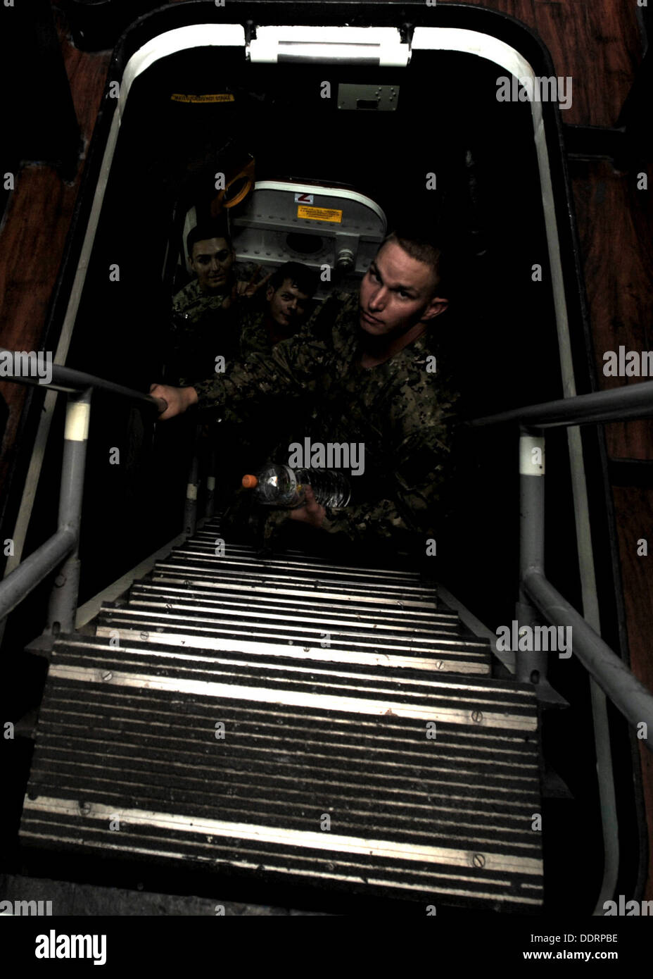 Seabees from Naval Mobile Construction Battalion (NMCB) 3 climb a ladderwell while touring USS Stethem (DDG 63). The shipboard - Stock Image