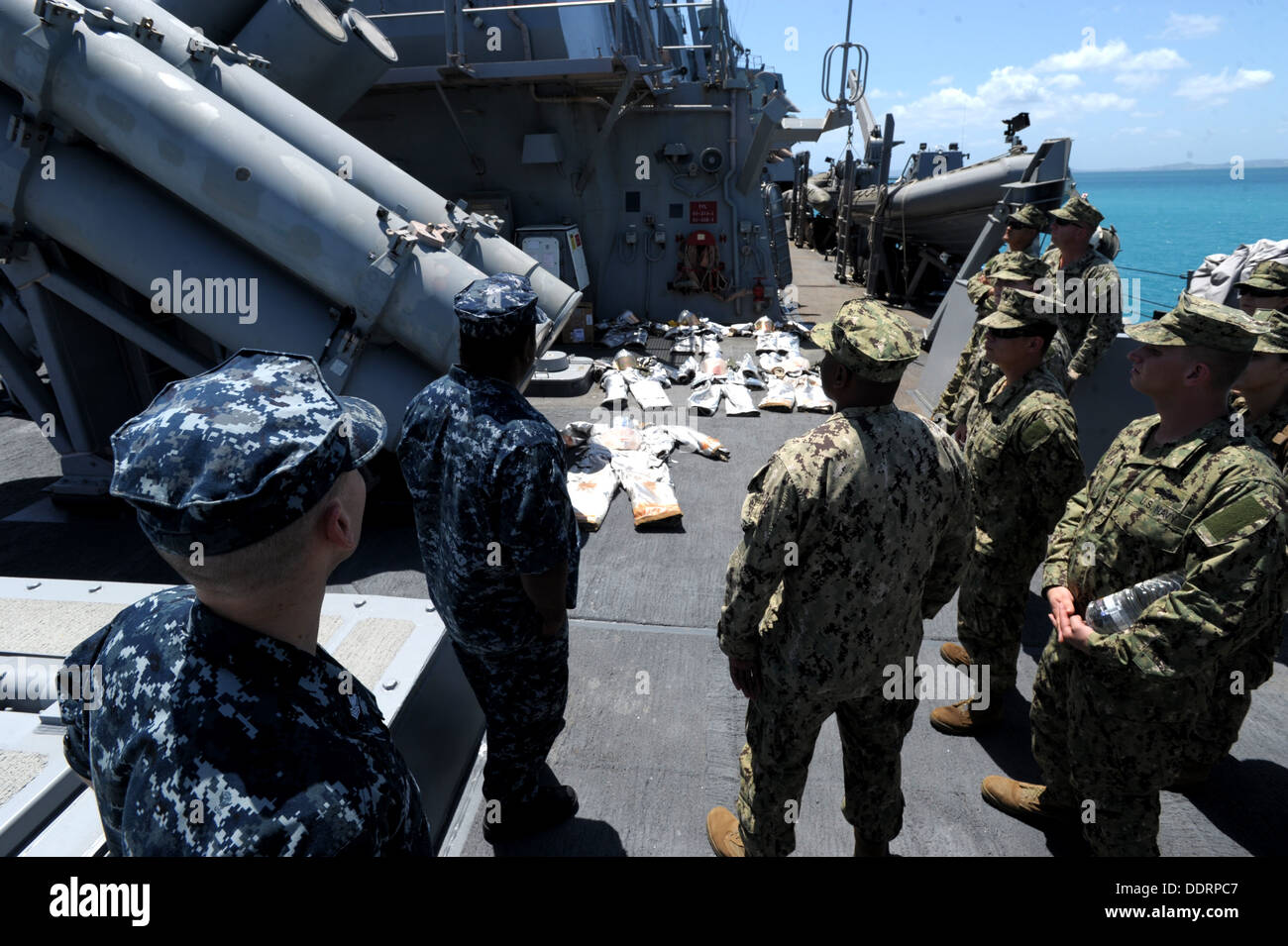 Seabees from Naval Mobile Construction Battalion (NMCB) 3 are shown donned-out fire-fighting equipment used to battle ship boar - Stock Image