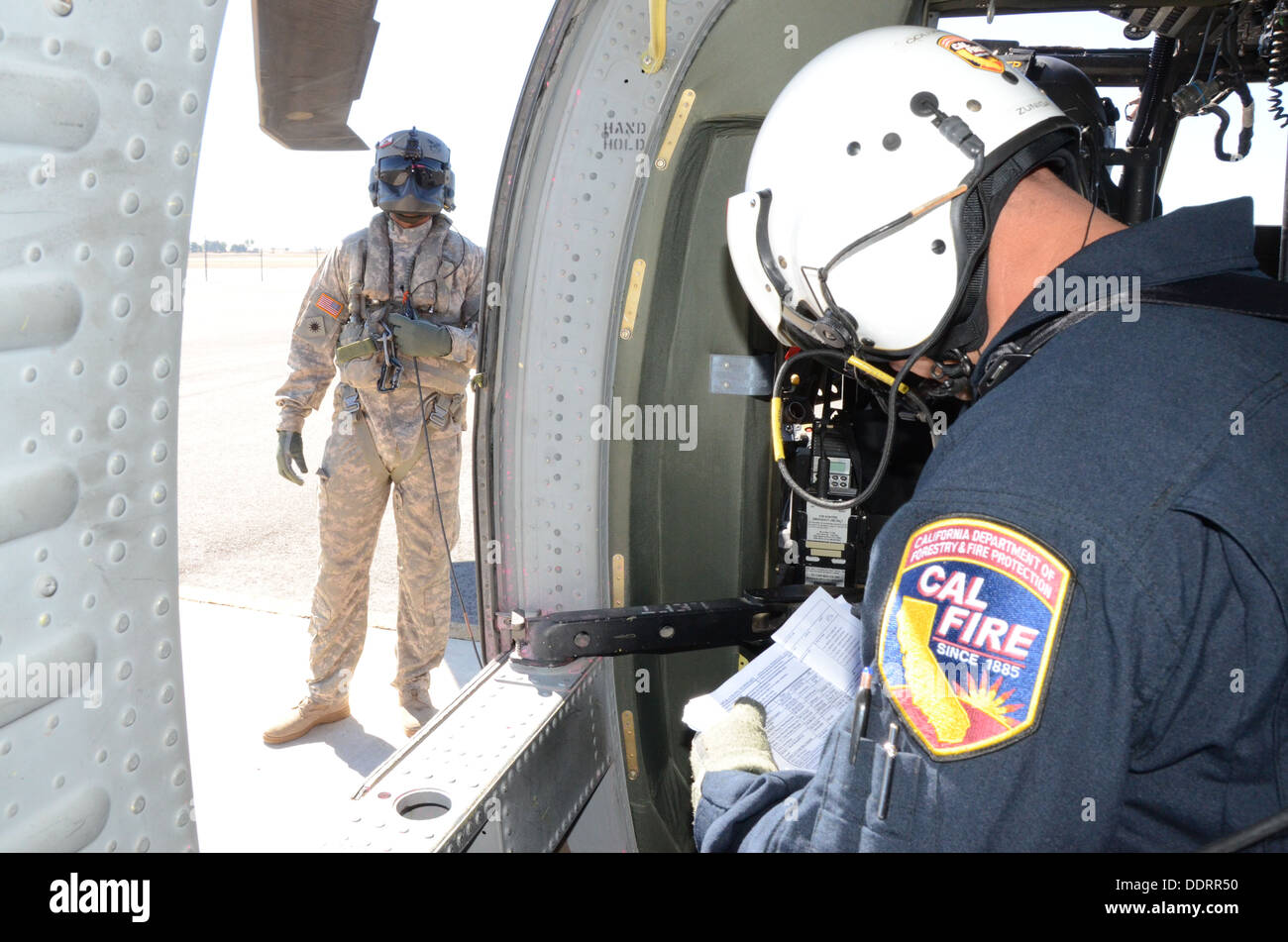 Cal Fire manager, Fire Capt. John Zungea, right, who spots U.S Forest Service fire fighters on the ground and Signals Spc. Michael Beatty, a UH-60 Black Hawk crew chief from the 1-140th Aviation Battalion (Air Assault), based out of Los Alamitos, prepare - Stock Image