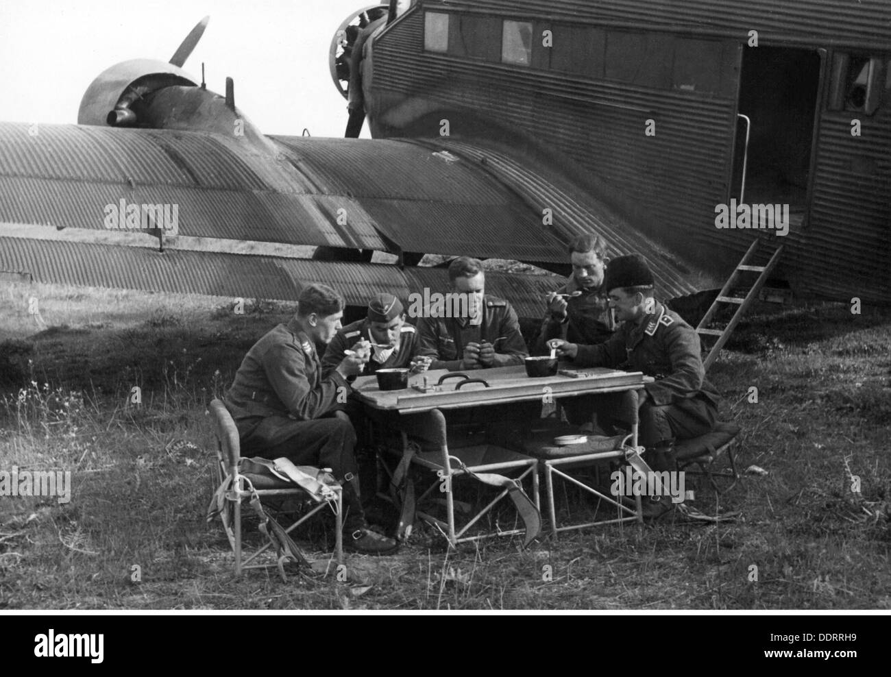 Second World War / WWII, Greece, German war correspondents of 3rd Air Force War Correspondent Company, during dinner besides an transport aircraft Junkers Ju 52, near Salonika, April 1941, journalist, journalists, propaganda company, soldiers, soldier, people, men, man, aeroplane, airplane, airplanes, aeroplanes, airfields, airfield, airstrip, strip, airstrips, strips, Luftwaffe (German Air Force), meal, meals, mess kit, seats, airline seat, the Balkans, Balkans campaign, communications zone, back area, rear echelon, Georg Schödl, German Reich, Third Reich, Mac, Additional-Rights-Clearences-NA - Stock Image