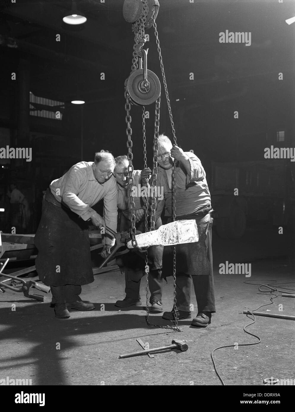 Three workers from Edgar Allen's handle a red hot billet, Sheffield, South Yorkshire, 1963. Artist: Michael Walters - Stock Image