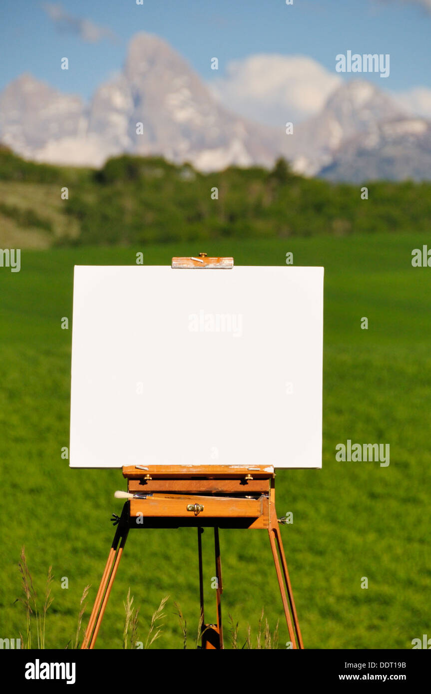 Easel overlooking blurred green field and mountain peaks - Stock Image