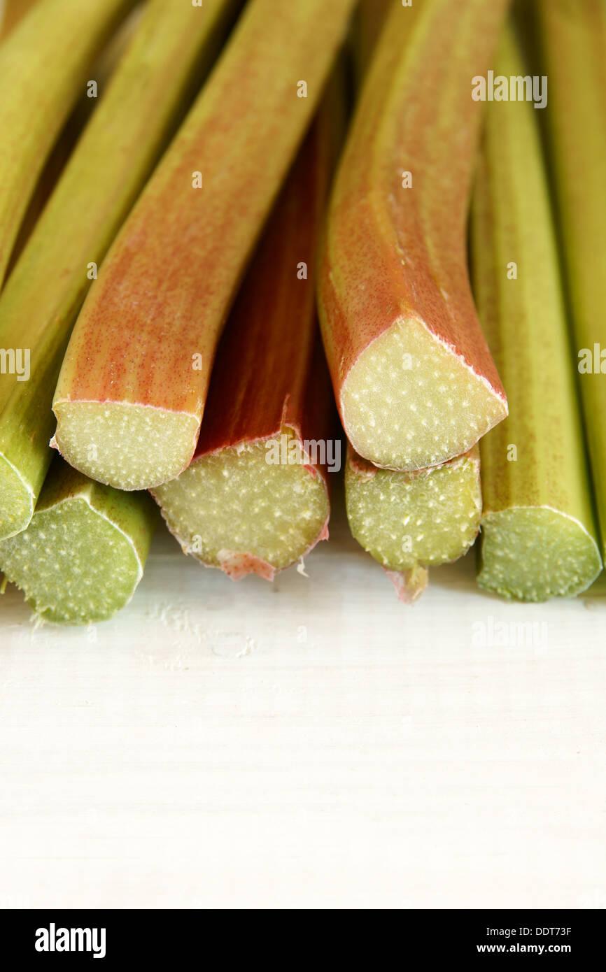 Freshly cut Rhubarb stems on a whitewash table - Stock Image