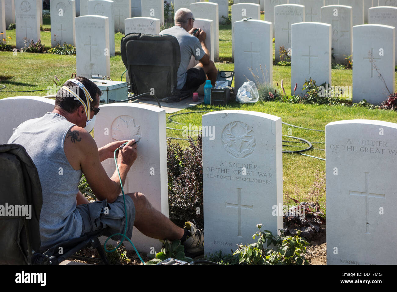 Engravers restoring headstones at Tyne Cot Cemetery of the Commonwealth War Graves Commission for World War One British soldiers - Stock Image