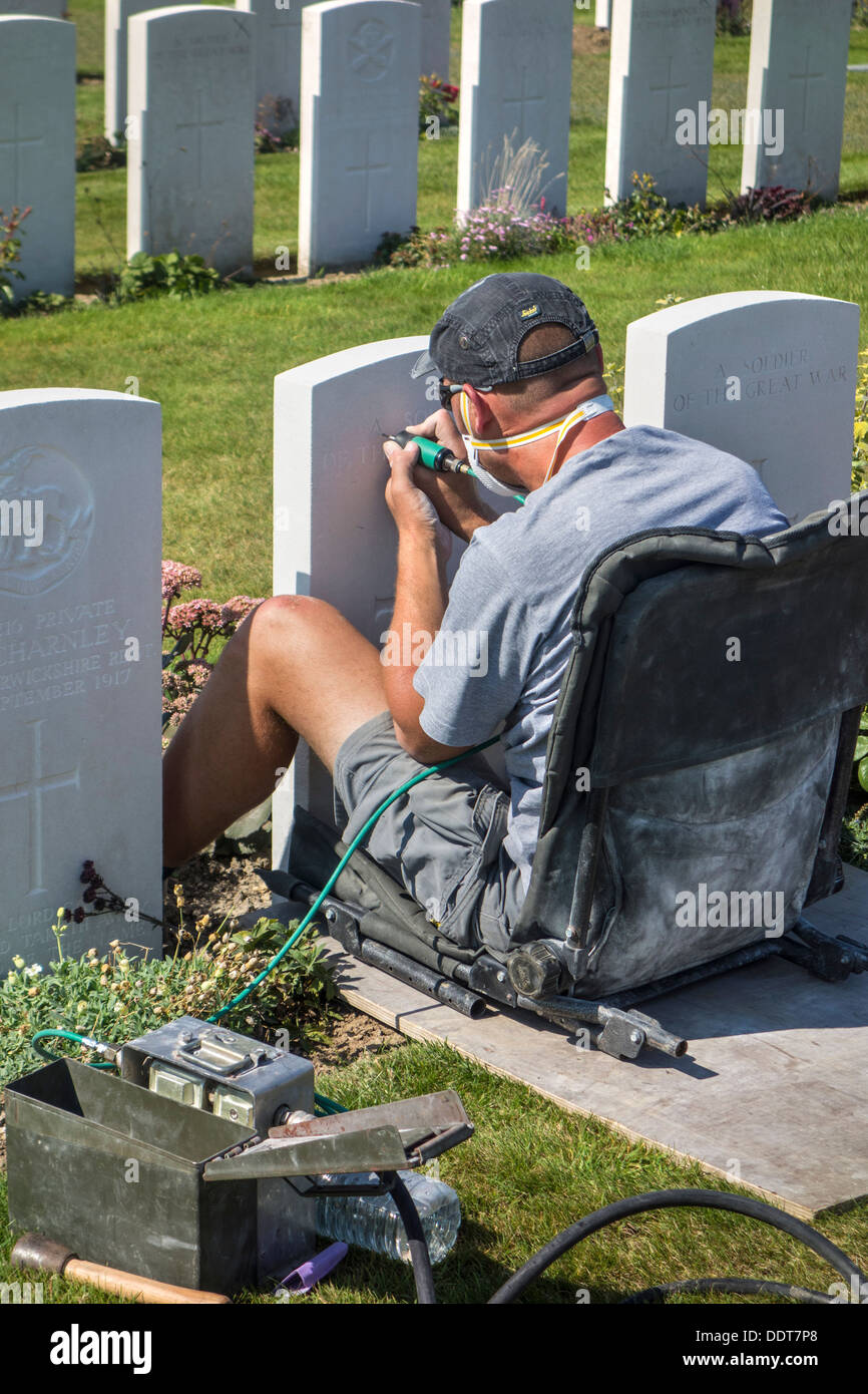Engraver restoring headstone at Tyne Cot Cemetery of the Commonwealth War Graves Commission for World War One British soldiers - Stock Image