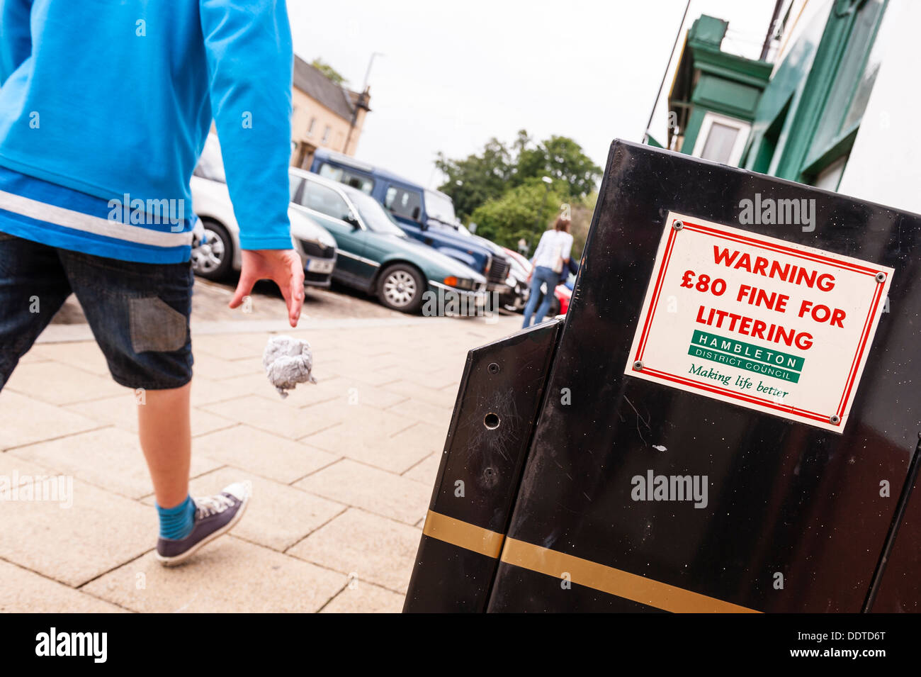 A boy throws litter on the ground as he walks past a bin warning of an £80 fine for littering in the Uk - Stock Image