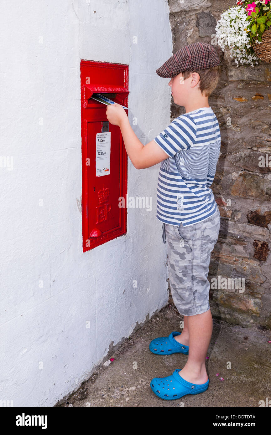 A boy of 9 posting a postcard in a Royal Mail Postbox in the Uk - Stock Image
