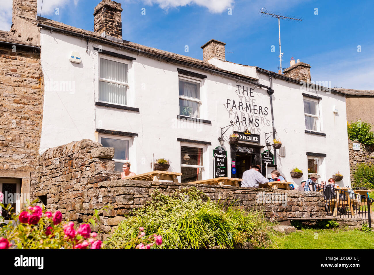 The Farmers Arms pub with people sitting outside at Muker in Swaledale , North Yorkshire , England, Britain, Uk - Stock Image