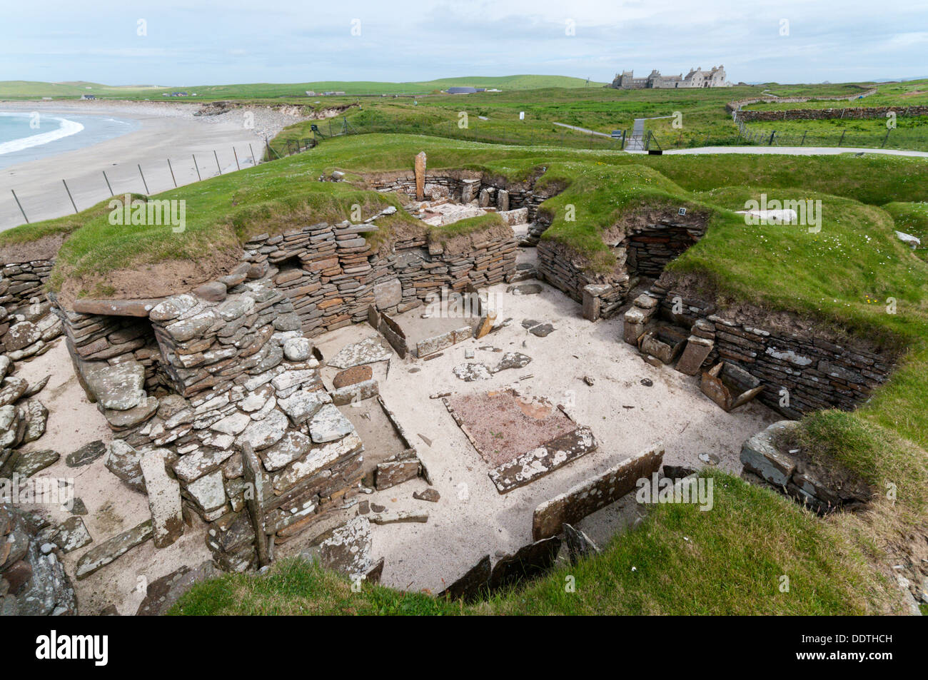 House 5 at Skara Brae Neolithic Village on Mainland Orkney with Skaill Bay and Skaill House in the background. Stock Photo