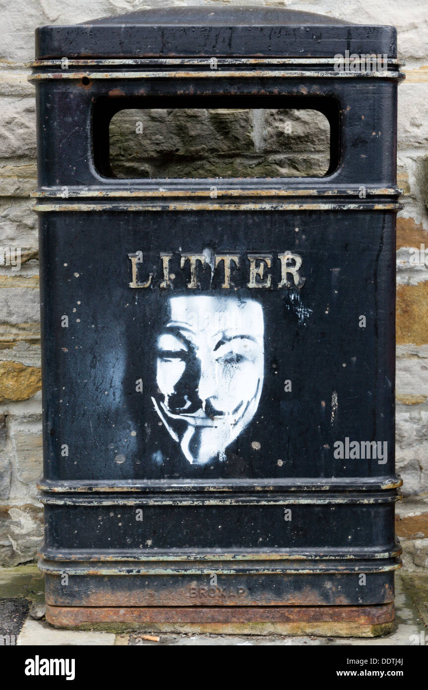 Stencil graffiti face on a litter bin. - Stock Image