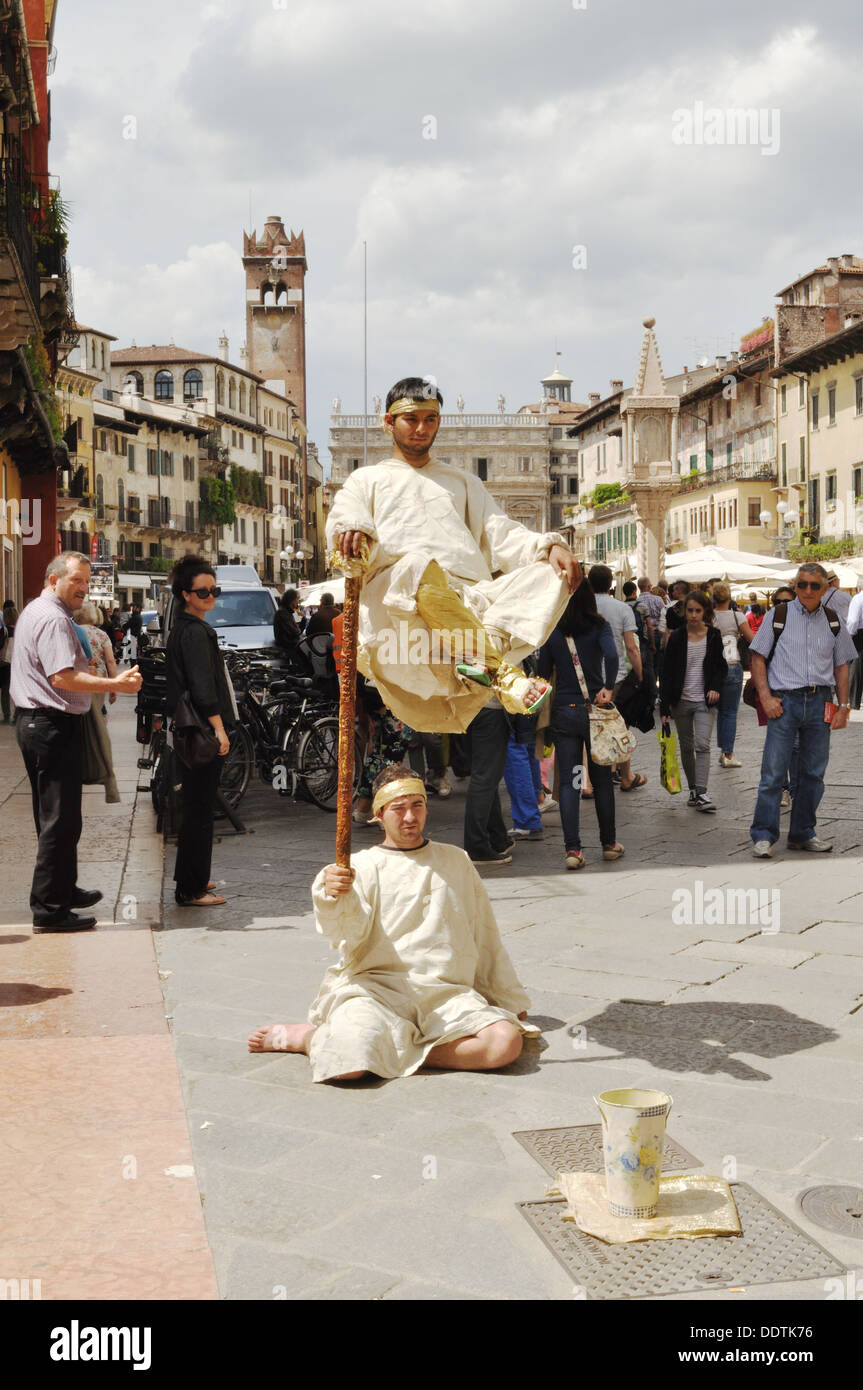 Two street entertainers perform a seemingly impossible feat in Verona. - Stock Image