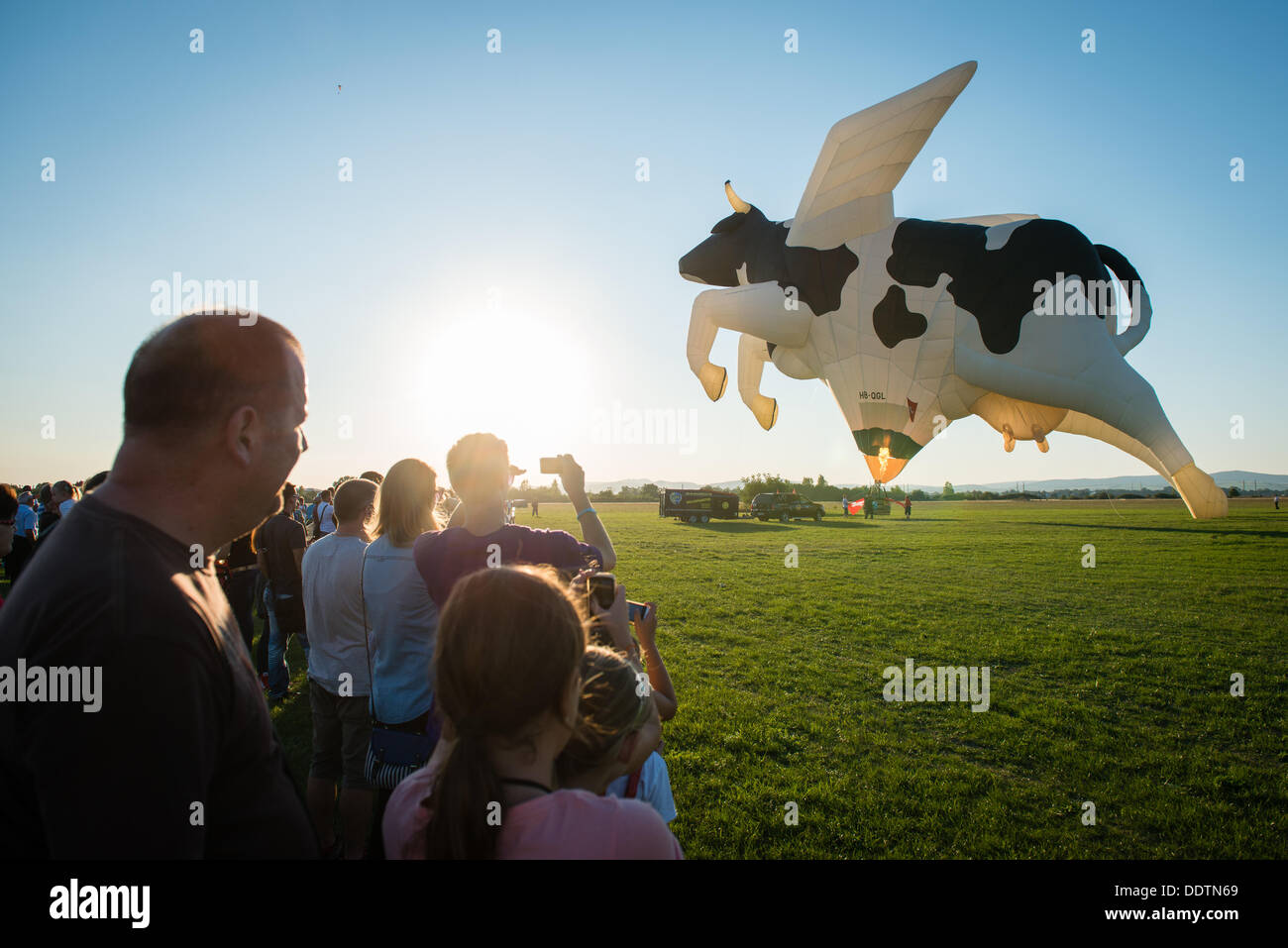 Piestany, Slovakia. 6th September 2013. Crowds watch as Swiss crew blast the flame into cow shape balloon during 1st Balloon megafiesta on September 6th, 2013 in Piestany, Slovakia Credit:  Lubos Paukeje/Alamy Live News Stock Photo