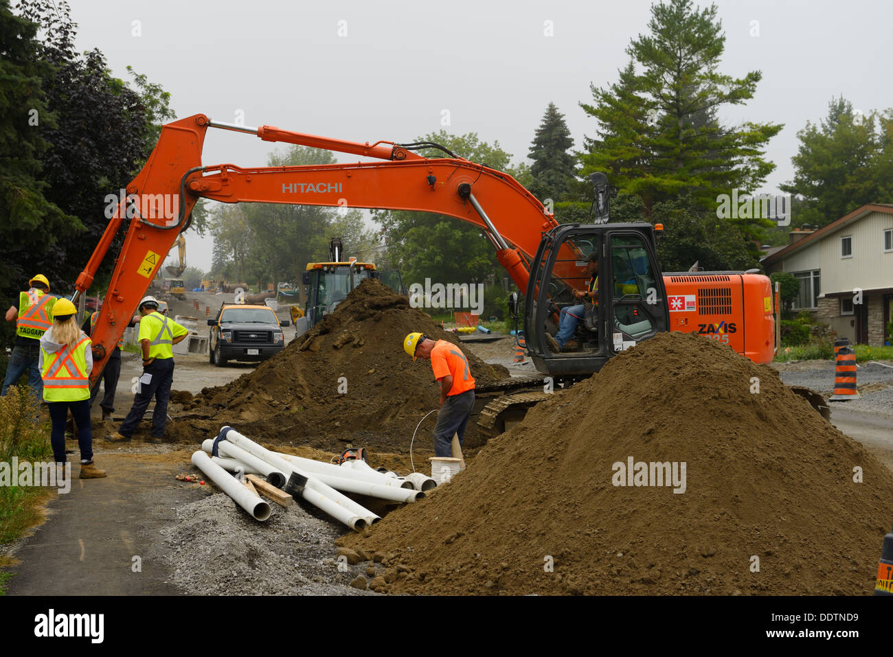 Construction crew at piles of earth at installation new sewers and watermains pipelines with power shovels and backhoe in Ottawa Canada - Stock Image