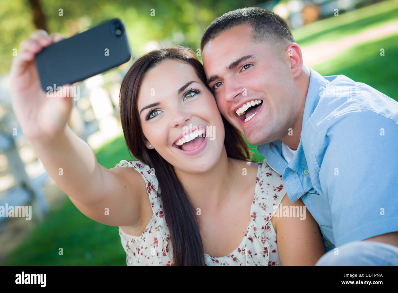 Happy Mixed Race Couple Taking Self Portrait with A Smart Phone in the Park. - Stock Image