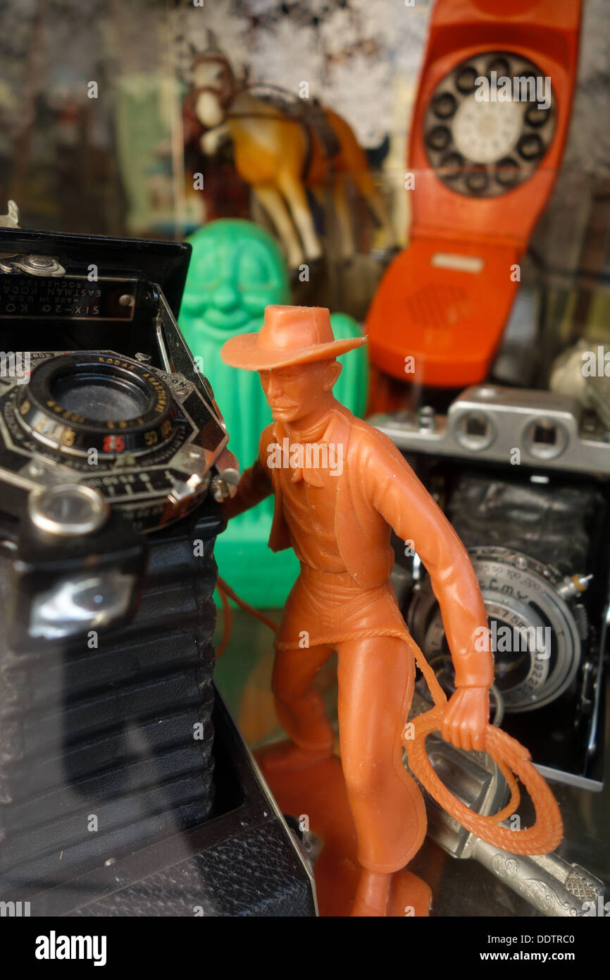A platic toy cowboy, an old, vintage camera, an old orange telephone and a toy horse in the window of a Pittsburgh antique shop - Stock Image