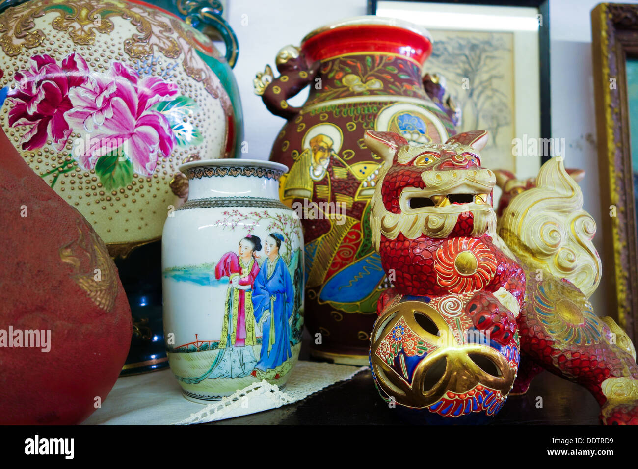 Various Asian or oriental style vases and figurines in an antique shop. - Stock Image