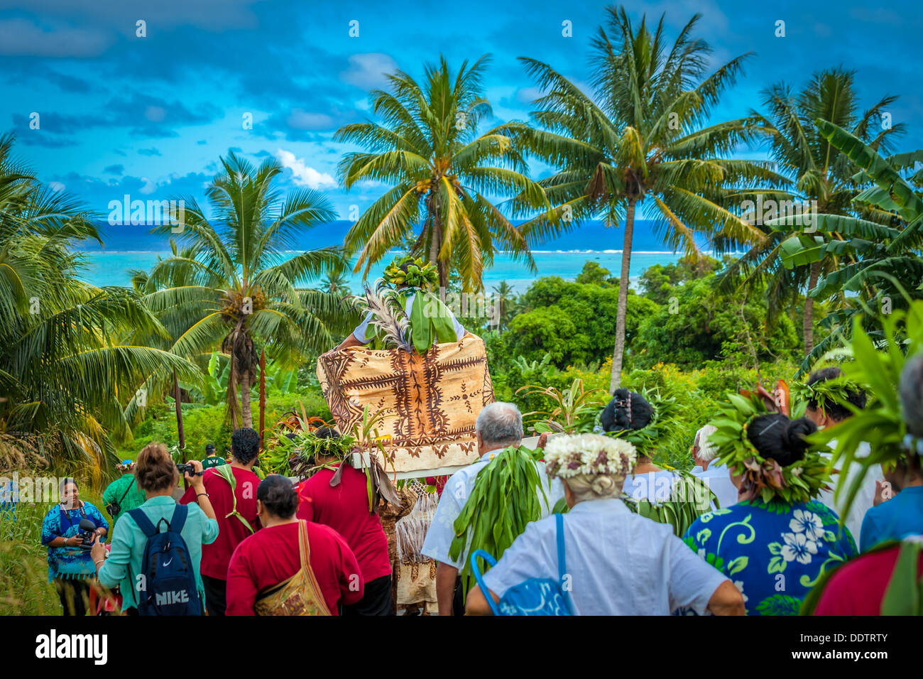 Aitutaki, Makirau Haurua in traditional costume being carried on a throne during his investiture - Cook Islands, South Pacific - Stock Image